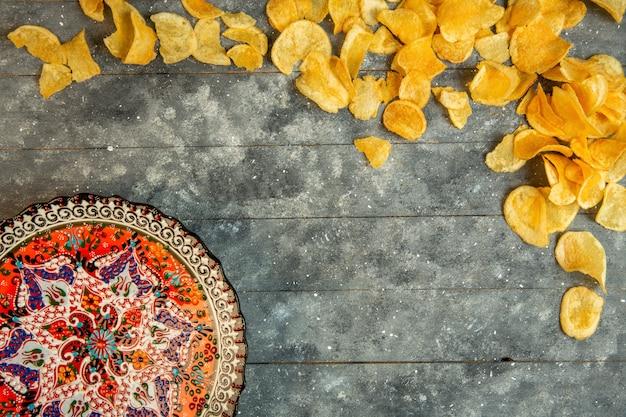 Вид сверху картофельных чипсов и тарелка с восточным принтом с копией пространства