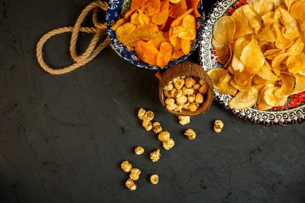 Вид сверху картофельные чипсы и попкорн в тарелку с восточным узором на черном