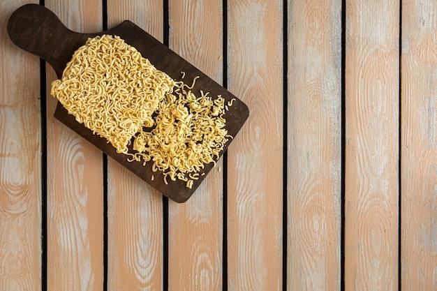 Вид сверху сырой лапши быстрого приготовления на деревянной разделочной доске