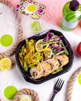 Вид сверху фаршированного куриного рулета с овощным чесноком и орехами, подается с салатом из капусты и ломтиком лимона в коробке доставки