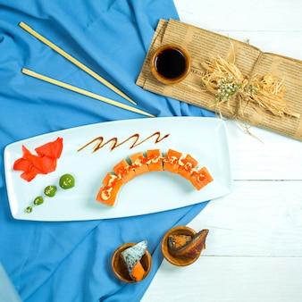 Вид сверху суши-ролла традиционной японской кухни с крабовым мясом, сливочным сыром и авокадо в икре летучей рыбы, подается с имбирем в соевом соусе и васаби на голубом