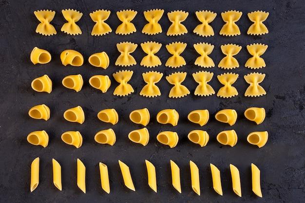 Вид сверху различных сырых макаронных изделий, расположенных на черном