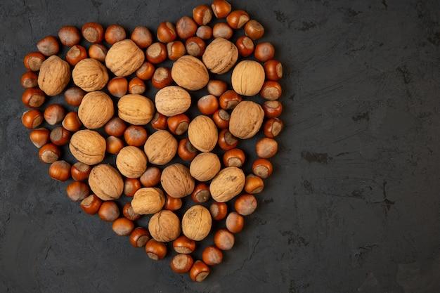 Вид сверху целых грецких и лесных орехов, расположенных в форме сердца на темном