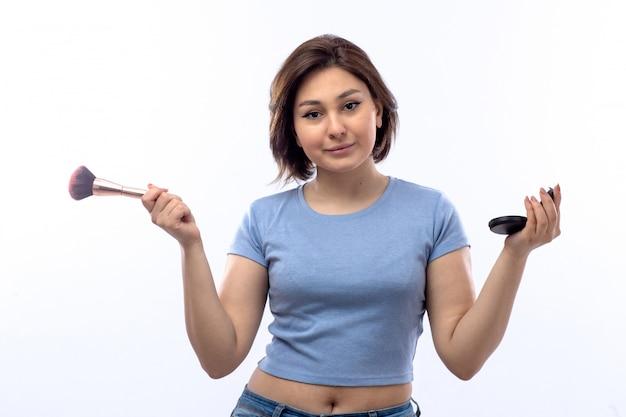 メイクをしている青いシャツの若い女性