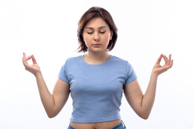 瞑想青いシャツの若い女性