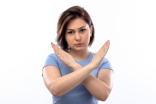 Молодая женщина в синей рубашке, показывая знак остановки