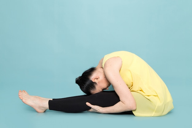 Молодая привлекательная дама в желтой рубашке и черных брюках делает позы йоги