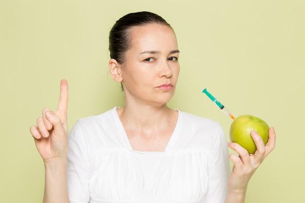 Молодая привлекательная женщина в белой рубашке держит зеленое яблоко со шприцем