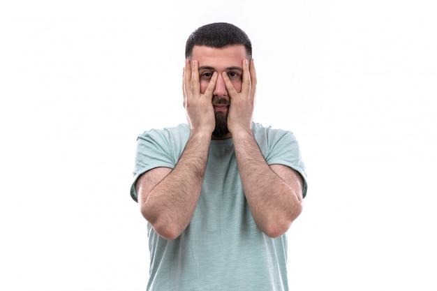 Молодой человек в синей футболке с бородой, обхватив руками лицо