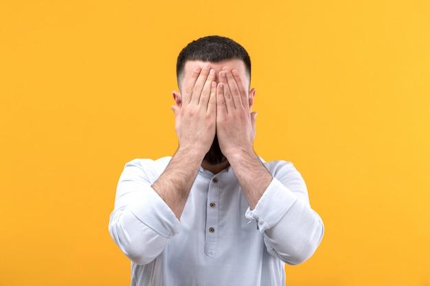 ひげの白いシャツの若い男荒廃した失望した表情