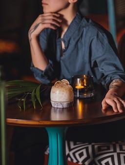 カクテルとろうそくの側面図でテーブルに座っている女性
