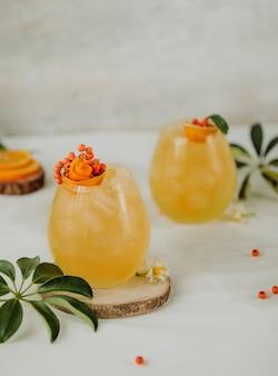 テーブルの上のグラスで海クロウメモドキとオレンジジュースと秋のカクテルの側面図
