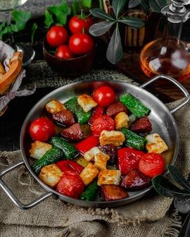 Жареная колбаса и овощи в сковороде