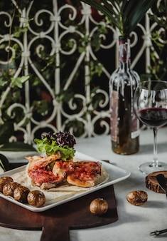 Вид сбоку жареной курицы с печеным картофелем на деревянной доске и стакан красного вина на столе