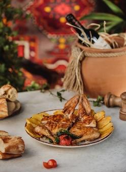 テーブルの上の皿にローストチキンベイクドポテトとグリル野菜の側面図