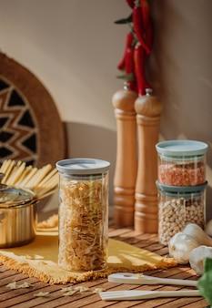 木製のテーブルに生ファルファッレパスタで満たされたガラスの瓶の側面図