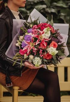 Вид сбоку женщины, держащей букет розовых роз и лилий с белым цветом цветка львиного зева, розовой гортензии, фиолетовой гвоздики и эустомы
