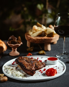 白い皿にケチャップと新鮮な玉ねぎと牛肉のグリルステーキの側面図