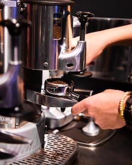 女性の手はコーヒーマシンで動作します