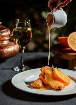 Вид сбоку чистого лимонного соуса на филе рыбы, украшенное ломтиком лимона