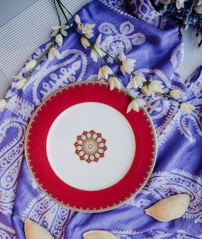Вид сверху керамической восточной тарелки с национальным рисунком на фиолетовом традиционном келагайском шелковом женском шарфе на стене