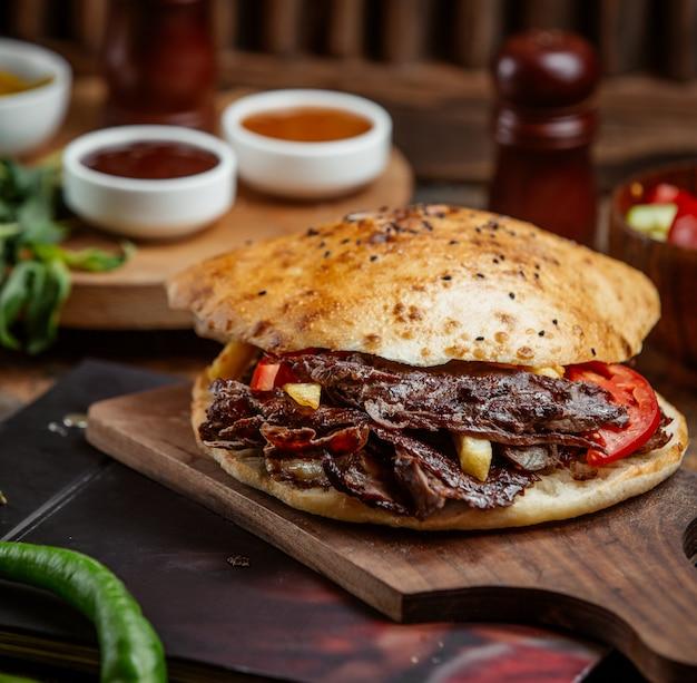 Донер из говядины с хлебом, фаршированным картофелем, картофелем фри на деревянной доске