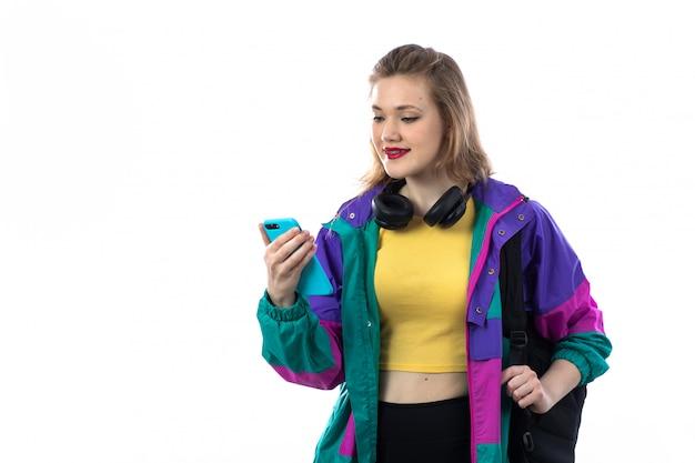 Красивая молодая женщина в красочной куртке и наушниках и с помощью смартфона