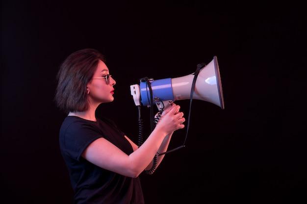 Молодая женщина в черной футболке держит мегафон