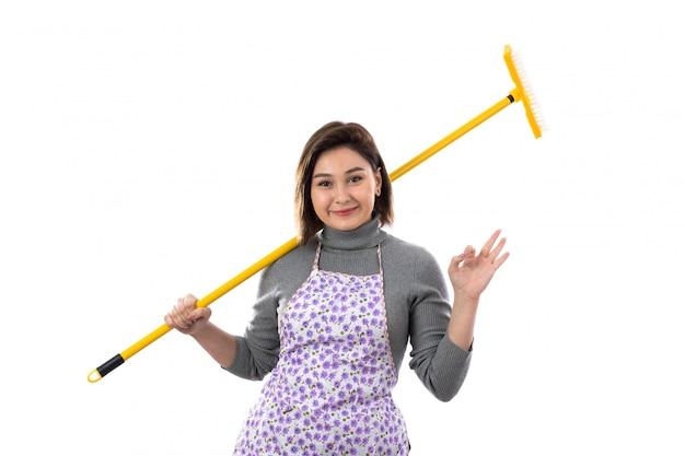 紫色のエプロンとモップを持つ女性