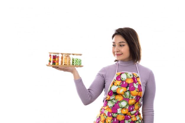キャンディーボトルを保持しているカラフルなエプロンを持つ女性