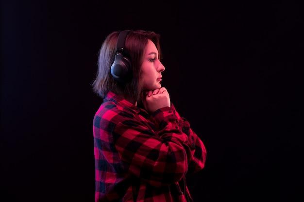 若い女性が市松模様の赤と黒のシャツでポーズ