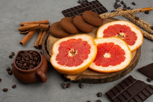 Вид спереди нарезанный цитрусовый спелый грейпфрут вместе с шоколадным печеньем и корицей на сером