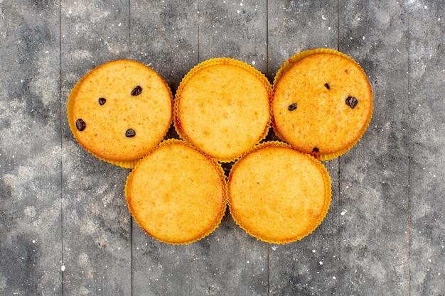 Вид сверху пирожные с шоколадными укусами круглого вкуснятина на сером