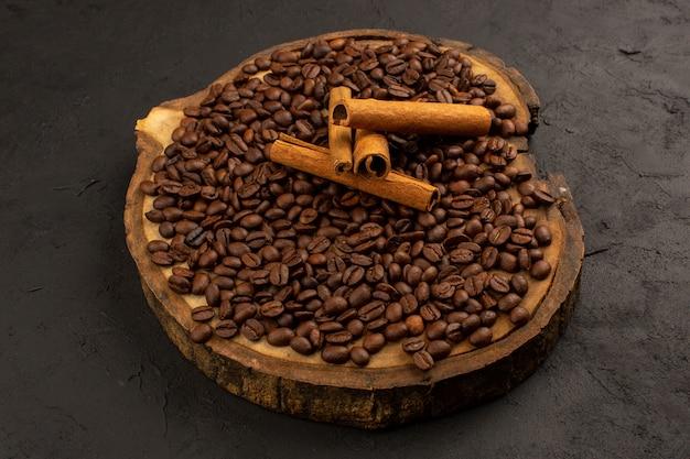 Семена кофе сверху коричневого цвета на коричневом деревянном столе и сером полу