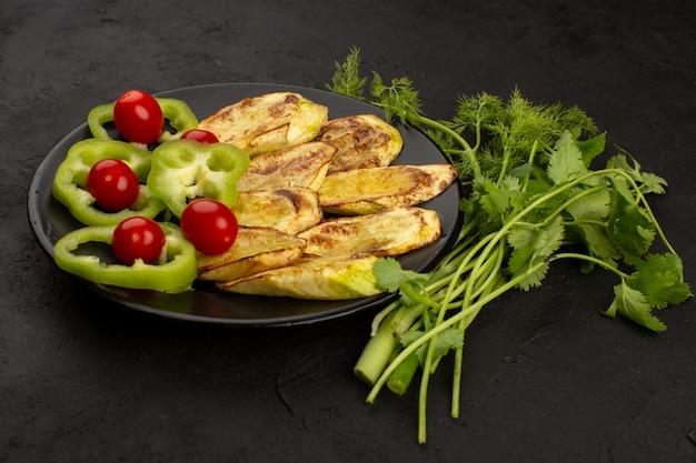 Вид сверху приготовленный баклажан вместе с красными помидорами черри нарезанный зеленый перец внутри черной тарелке на темном фоне