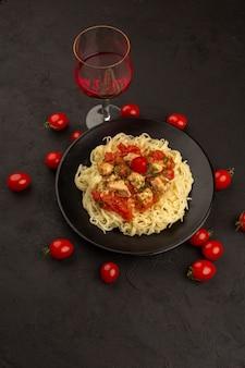 トップビュー手羽先とトマトソースのパスタを暗い床の黒いプレート内に調理