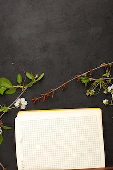 暗い机の上の花と一緒にトップビューコピーブック