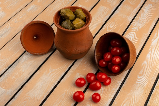Долма вместе с красными помидорами черри в коричневых горшках на деревянном столе
