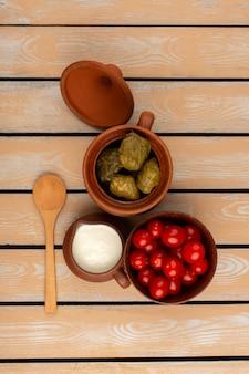 Вид сверху долма вместе с йогуртом и красными помидорами черри на деревянном