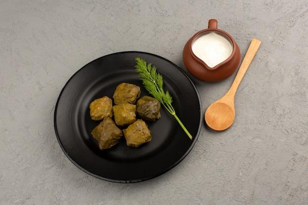 グレーのヨーグルトと一緒に黒いプレートの内側においしい肉と上面図ドルマ