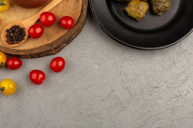 Вид сверху долма с помидорами внутри черной пластины на сером полу