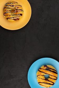 Вид сверху пончики сладкие вкусные вкусные внутри цветные тарелки на темном фоне