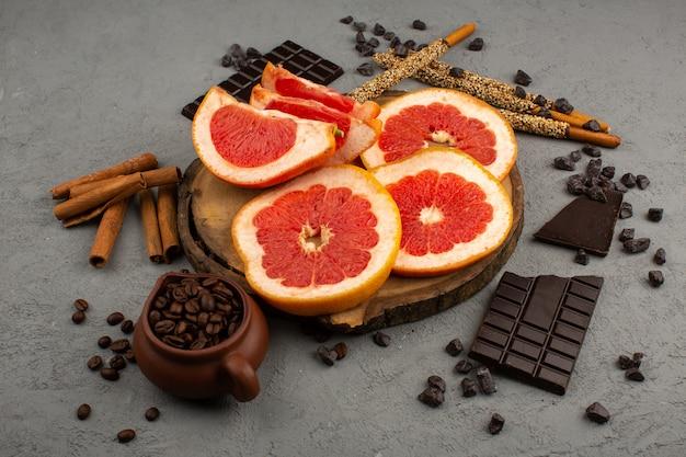 Сочный грейпфрутовый ломтик сверху вместе с корицей и шоколадными батончиками на сером полу