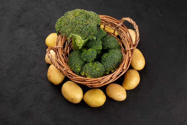 Вид сверху зеленый брокколи свежий с очищенной картошкой на темном полу