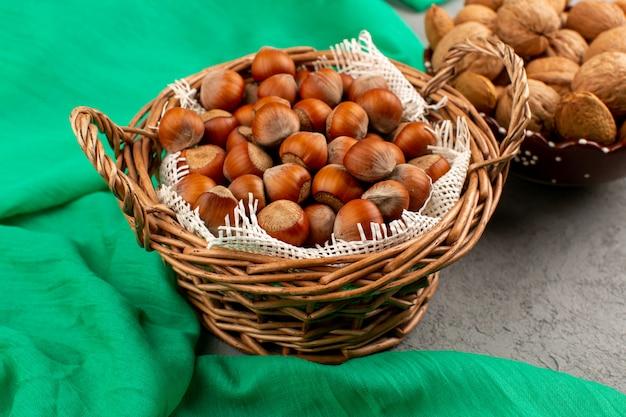 Вид сверху фундука и грецких орехов в корзинах на зеленой ткани и серый