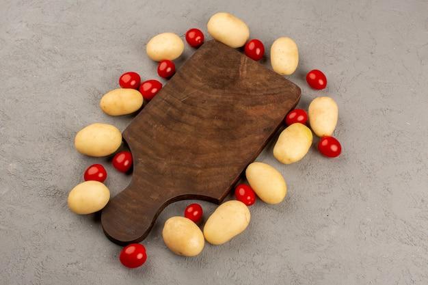 Вид сверху на подкладке из картофеля помидоры свежие спелые на сером полу
