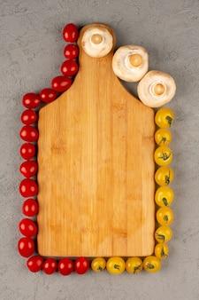 灰色の背景に黄色の赤いトマトやキノコなどの野菜が並ぶ平面図