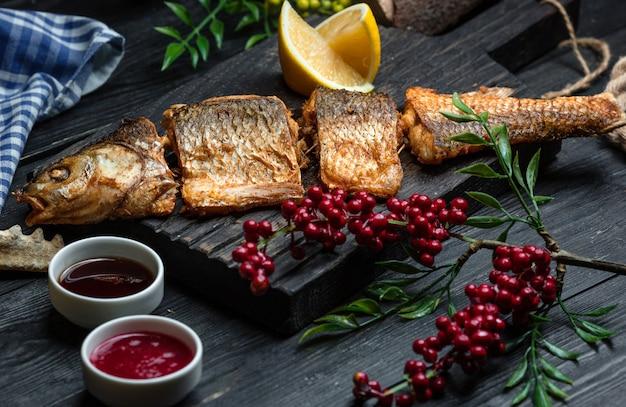 木の板にクランベリーと魚のフライ