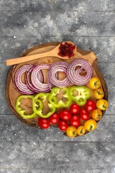 Вид сверху лук помидоры перец нарезанный и целые на сером полу