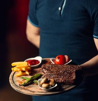 Жареный стейк с картофелем фри на деревянной доске